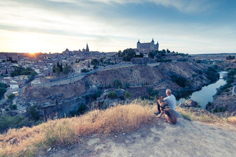 Reisendmann und -hund, die Toledo-Stadtbild vom Hügel aufpassen stockbilder