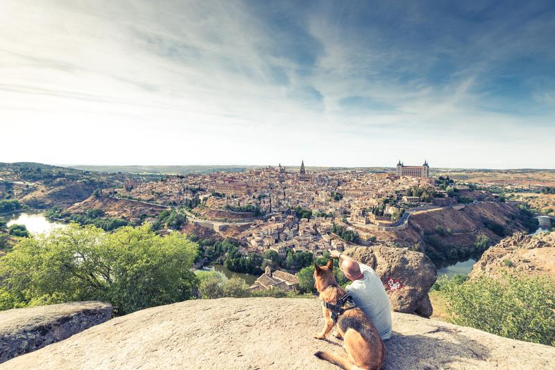 Reisendmann und -hund, die Toledo-Stadtbild vom Hügel aufpassen lizenzfreie stockbilder