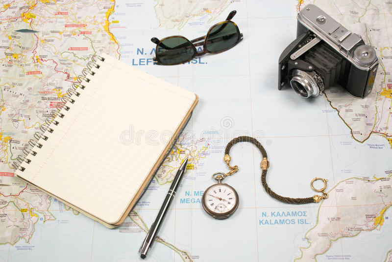 Reisepläne mit Karte von Insel Griechenland und von Gegenständen Kamera, Sonnenbrilletaschenuhr und Notizbuch lizenzfreies stockbild
