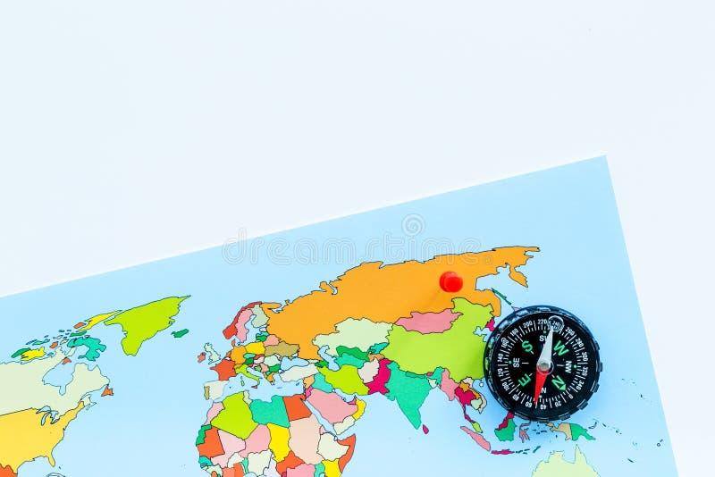 Reiserichtungs- und Reiseplanungskonzept mit Kompass und Karte der Welt auf weißem Draufsichtraum des Hintergrundes für Text lizenzfreies stockbild