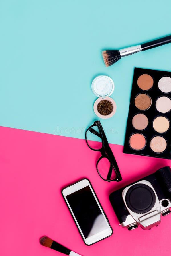 Reisezubehör der flachen Lagefrauen auf buntem blauem und rosa Hintergrund mit Kosmetik, Smartphone, Gläsern und Kamera lizenzfreies stockfoto
