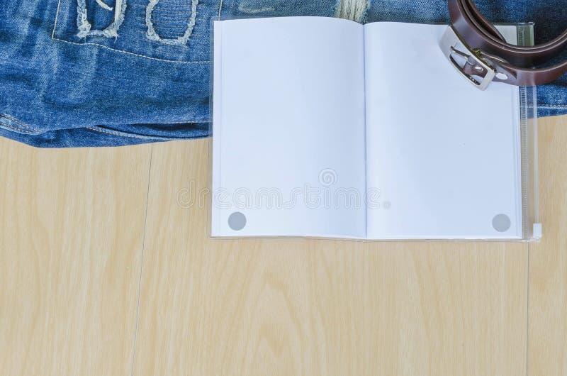 Reisezubehör und -kostüm auf Holzfußboden, Jeans, Buch, Gurt lizenzfreies stockfoto