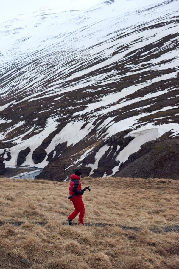 Reisfotograaf die op het gebied van IJsland dichtbij berg lopen stock fotografie
