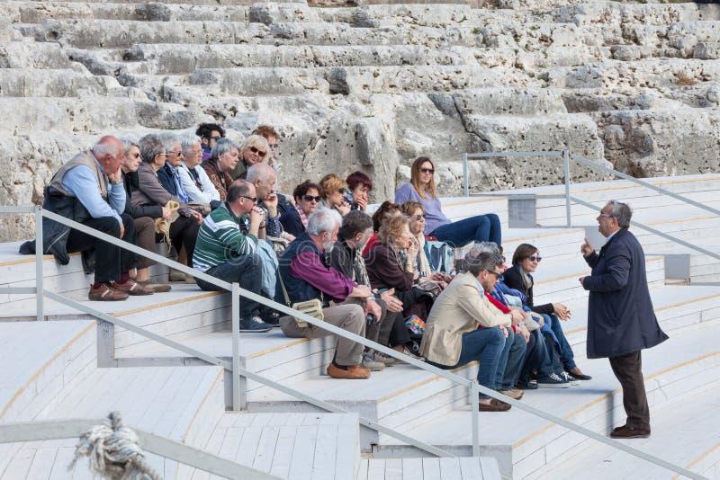 Reisgids met groep toeristen die op oude stappen zitten royalty-vrije stock foto