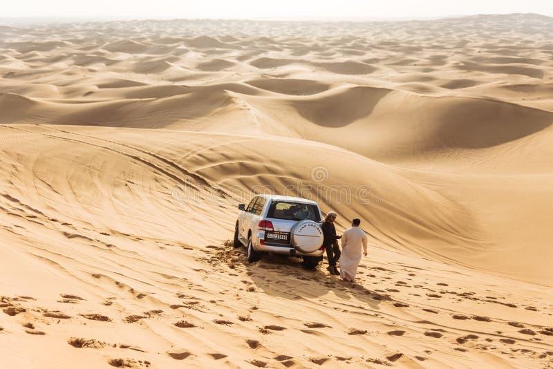Reisgidsmensen met vierwielige aandrijvingsauto op de grote woestijn in Doubai stock fotografie