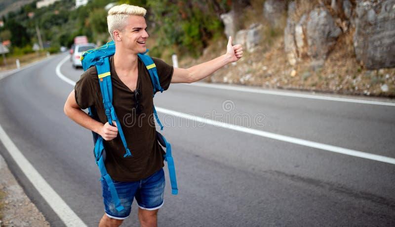 Reismens backpacking die op wegreis liften die een rit van auto hitching stock foto's
