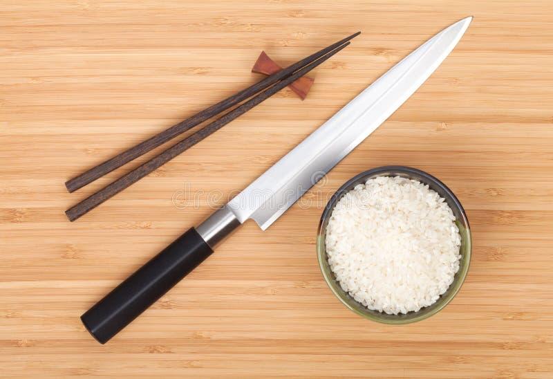 Reisschale, Essstäbchen und Sushimesser lizenzfreies stockbild