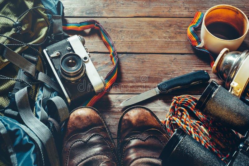 Reistoebehoren op Houten Achtergrond, Hoogste Mening De oude laarzen van het wandelingsleer, rugzak, uitstekend filmcamera en mes stock foto