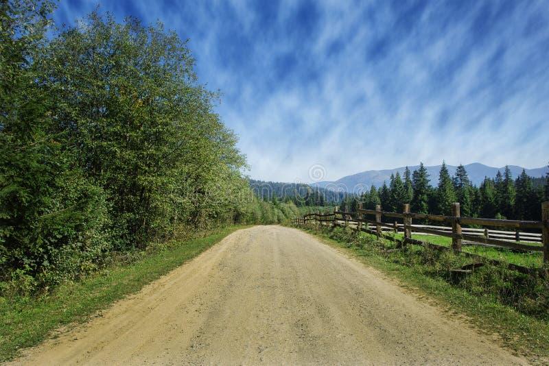Reisweg op het gebied met groen gras en blauwe hemel met wolken op het landbouwbedrijf in mooie de zomer zonnige dag Schoon, idyl stock afbeeldingen