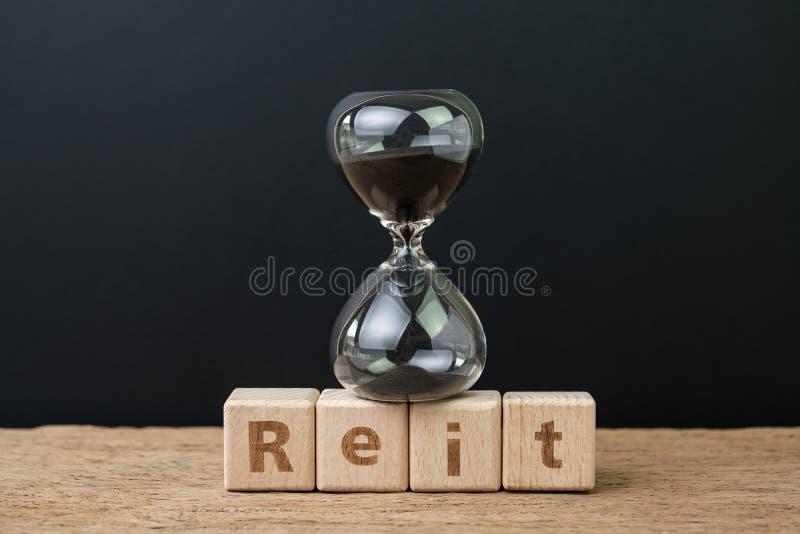 REIT,不动产投资信托兴旺的时间概念、sandglass或者滴漏在木立方体块与字母表修造 库存图片