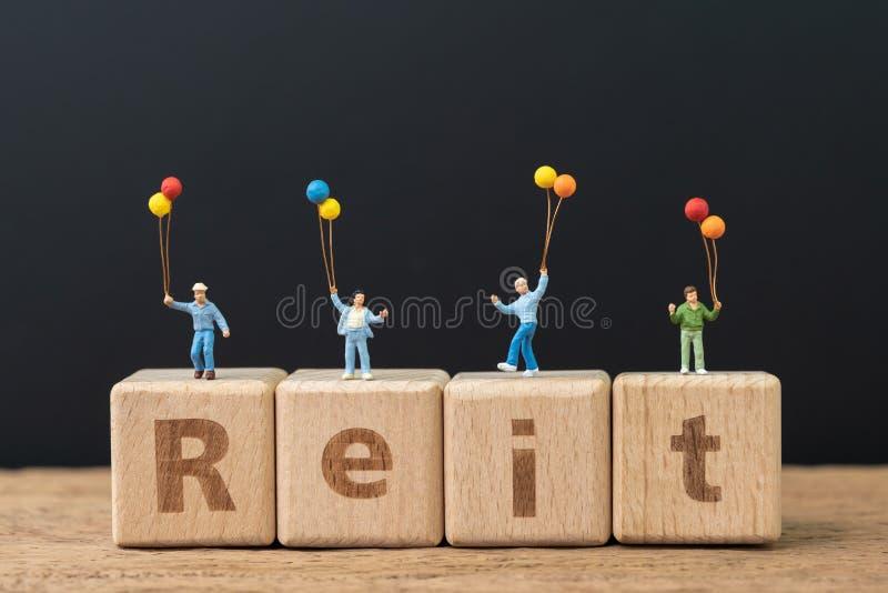 Reit begrepp för fastighetsinvesteringförtroende, lyckligt miniatyrfolk som rymmer ballonger på kubträkvarteret med alfabetsamman royaltyfria foton