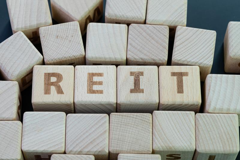 Reit, nieruchomość funduszu inwestycyjnego pojęcie, sześcianu drewniany blok z abecadłem buduje słowo REIT na blackboard zdjęcia royalty free