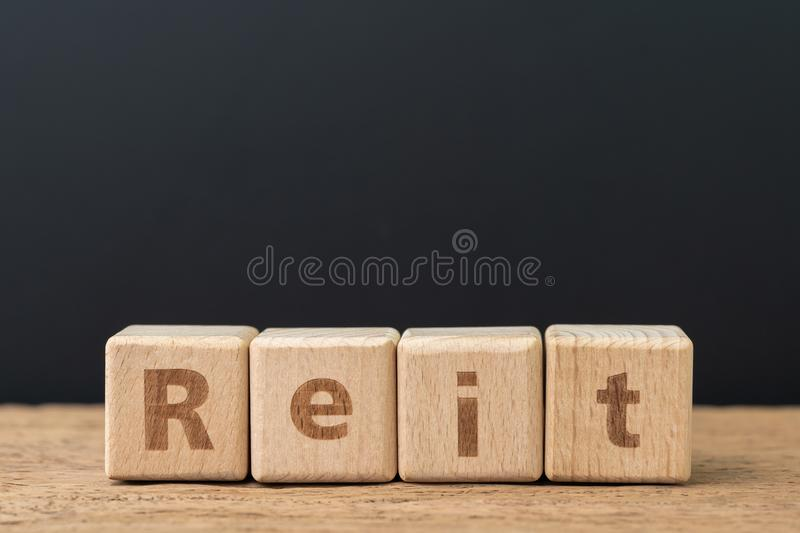 Reit, Real estate investment trust concept, cube wooden block with alphabet combine the word Reit on dark black background.  stock photos