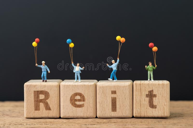 Reit, Real estate investment trust concept, happy miniature people holding balloons on cube wooden block with alphabet combine the royalty free stock photos