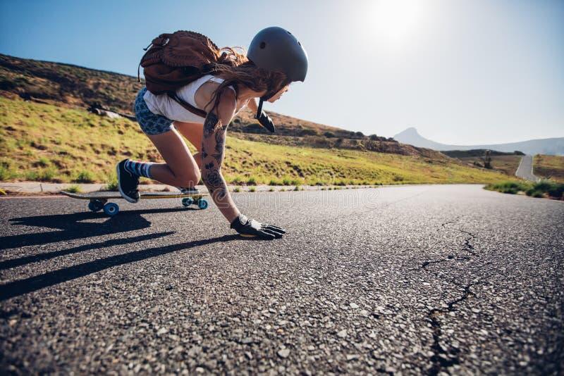 Reiten der jungen Frau auf ihrem Skateboard stockfoto