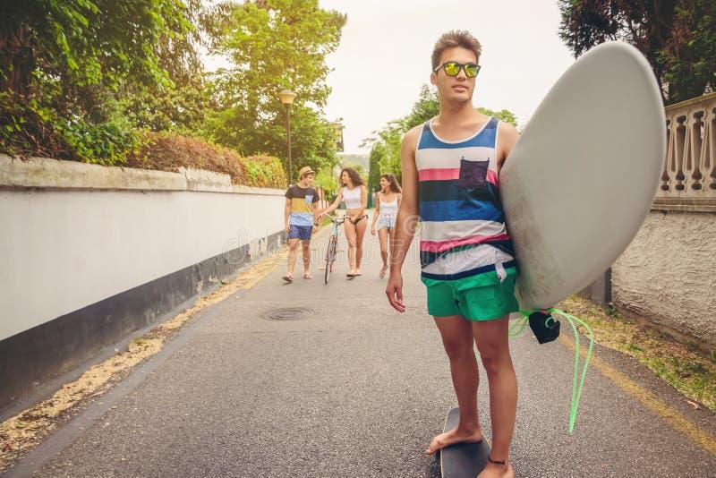 Reiten des jungen Mannes auf Rochen und Holdingsurfbrett stockfoto