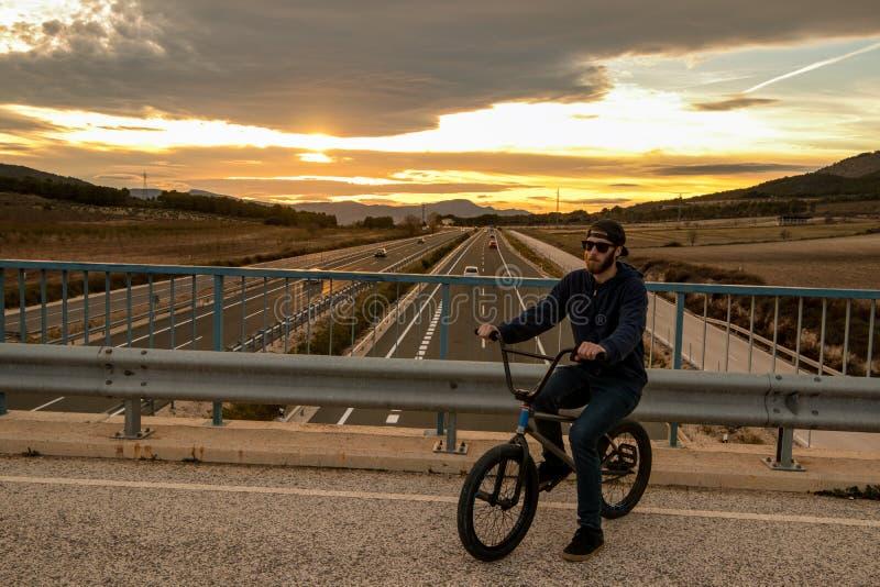 Reiten des jungen Mannes ein bmx Fahrrad Bmx Mitfahrer Städtischer Sport lizenzfreie stockfotos
