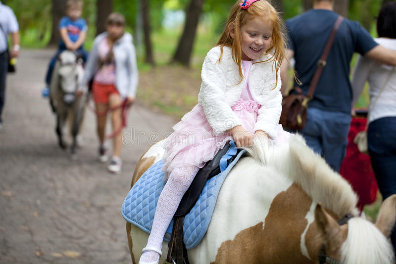 Reiten des kleinen Mädchens auf einem Pony in einem Stadtpark stockbilder