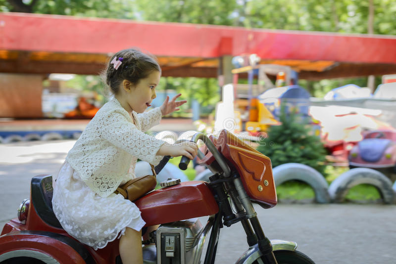 Reiten des kleinen Mädchens auf motobike stockfotografie