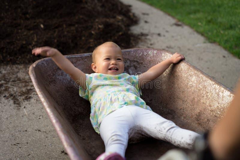 Reiten des kleinen Mädchens im Radkarren lizenzfreies stockfoto