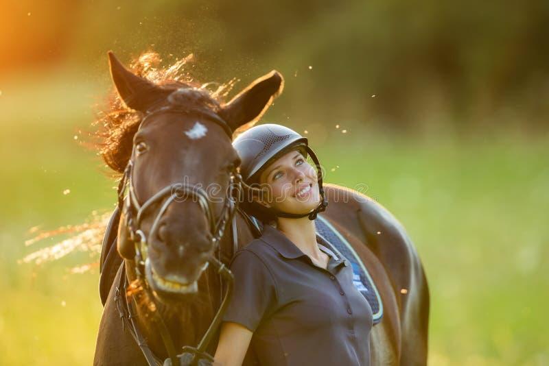 Reiter der jungen Frau mit ihrem Pferd, das gute Laune genießt stockfotografie