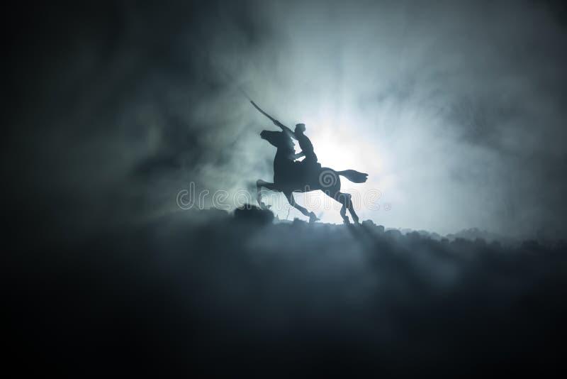 Reiter des Weltkrieg-Offiziers (oder Kriegers) auf Pferd mit einer Klinge bereit zu kämpfen und Soldaten auf einem dunklen nebeli stockfoto