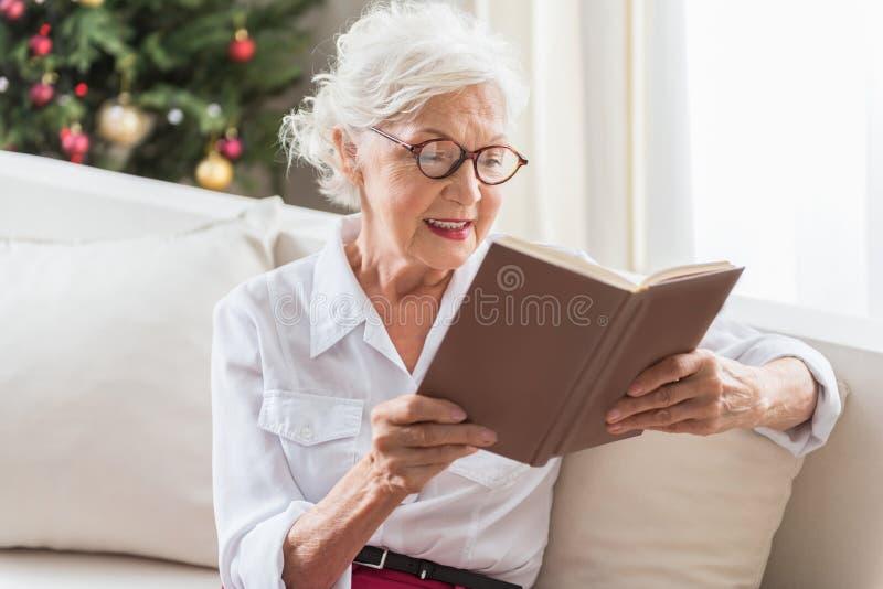 Reizend ältere Frau steht zu Hause still stockfotos