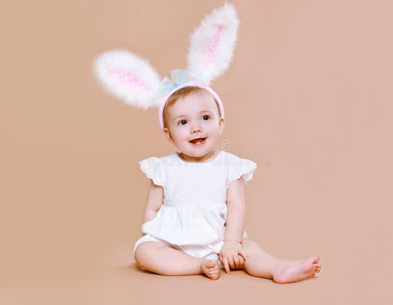 Reizend Baby, das in KostümOsterhasen sitzt stockfotografie