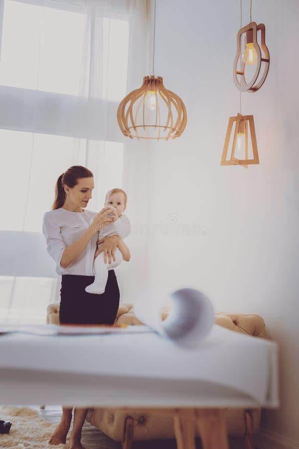 Reizend Babysitter, der kleine süße Babystellung im großen Raum pflegt stockbilder