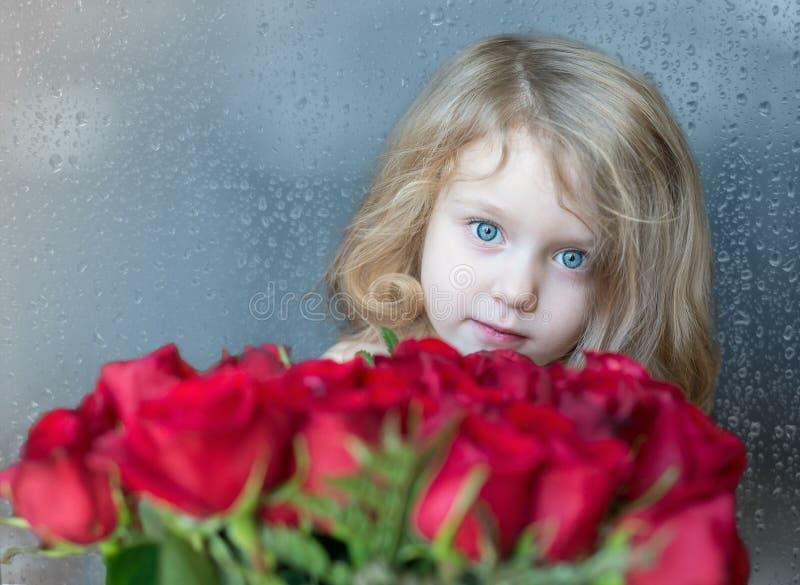 Reizend blondes kaukasisches Mädchen, das von hinten rote Rosen schaut Die natürlichen Regentropfen auf dem Fenster als Hintergru stockfoto