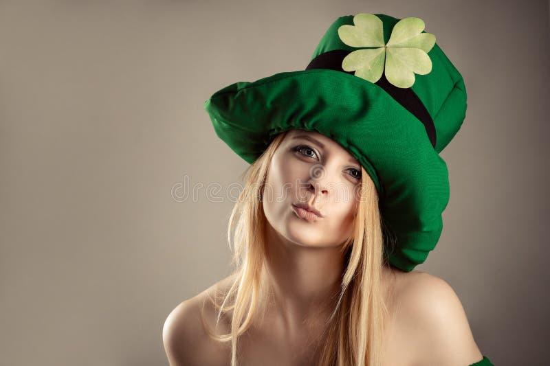 Reizend blondes Mädchen im Bild des Kobolds mit Luftkussgeste stockfotografie