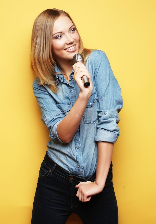 Reizend Blondine, die mit Mikrofon im Studio über yel singen stockfotos