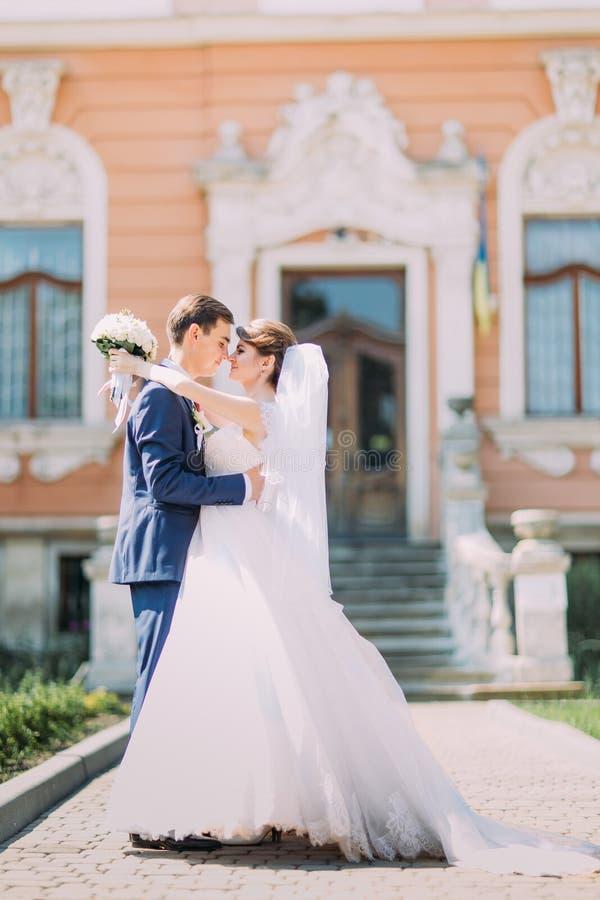 Reizend Braut des romantischen eben verheirateten Paars und stilvoller Bräutigam, die vor antikem Gebäudeeingang sich hält stockfotografie