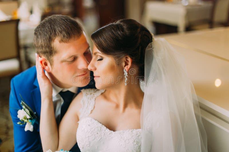Reizend Braut im schönen weißen Kleid ihren stilvollen gekleideten Bräutigam leicht küssend Nahaufnahme lizenzfreies stockbild