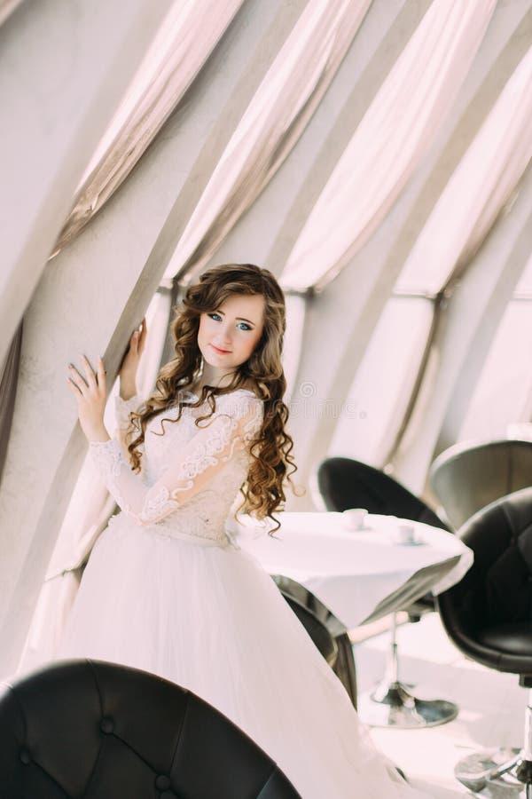 Reizend Braut im weißen Kleid und mit der gelockten Frisur, die nahe Fenster am Café aufwirft stockfotografie