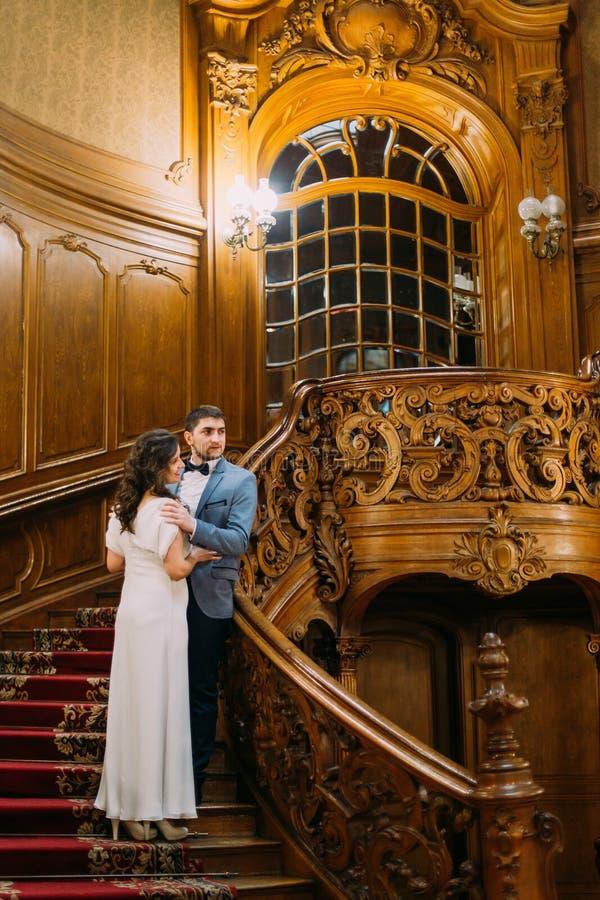 Reizend Braut und hübscher eleganter Bräutigam, die auf alter Treppe mit dem Hintergrund der herrlichen hölzernen Weinlese umfass stockbild
