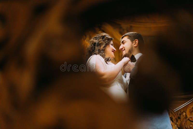 Reizend Braut und hübscher eleganter Bräutigam, die an in herrlichen hölzernen Weinleseinnenraum tanzt Ansicht von der Balustrade stockfotografie