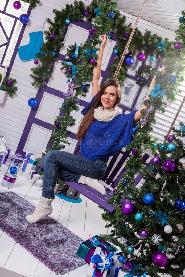 Reizend Brunette in den Jeans und in einer blauen Strickjacke sitzt auf einem Schwingen an stockfotografie