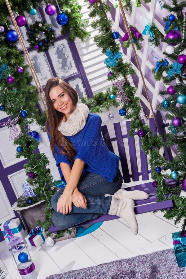 Reizend Brunette in den Jeans und in einer blauen Strickjacke sitzt auf einem Schwingen an lizenzfreie stockfotografie