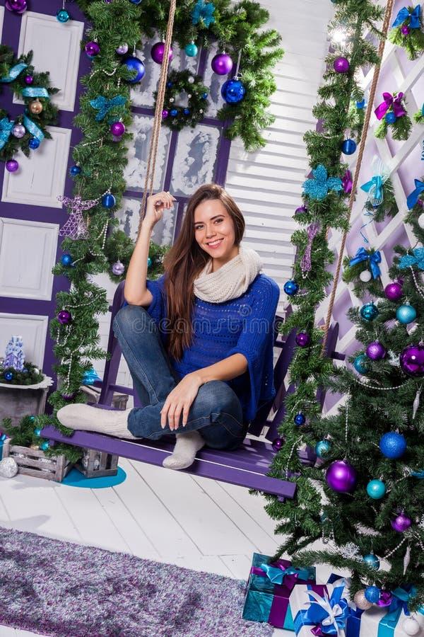Reizend Brunette in den Jeans und in einer blauen Strickjacke sitzt auf einem Schwingen an stockbild