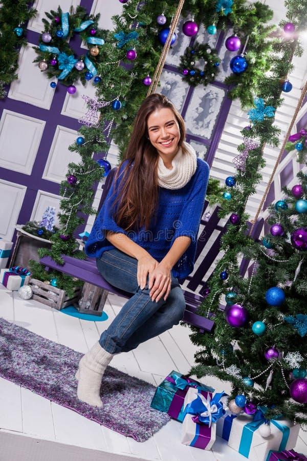 Reizend Brunette in den Jeans und in einer blauen Strickjacke sitzt auf einem Schwingen an lizenzfreies stockbild