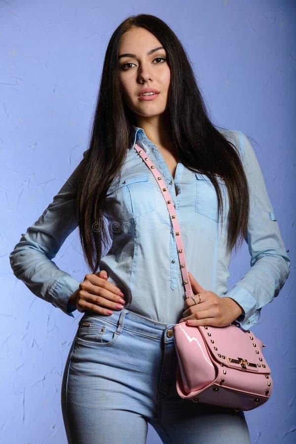 Reizend Brunette mit dem langen Haar, das eine rosa Handtasche hält lizenzfreie stockfotografie