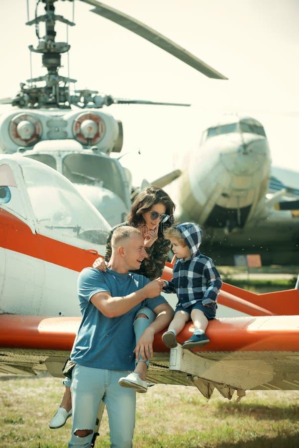 Reizend concept De familie bij retro vliegtuigen parkeerde op grond, het reizen Het kind met moeder en vaderbezoeklucht toont royalty-vrije stock afbeeldingen