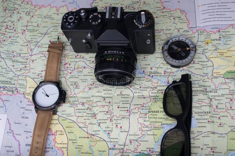 Reizend concept Uitstekende camera met kompas en oogglazen op de achtergrond van de wereldkaart royalty-vrije stock afbeelding