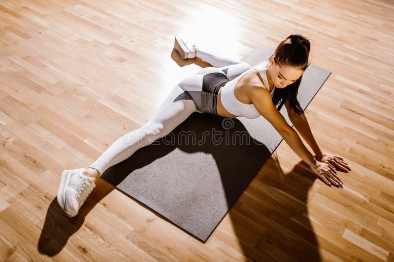 Reizend dünnes dunkelhaariges Mädchen kleidete weiße Sportspitze und Strumpfhosen tut das Ausdehnen auf die Matte für Eignung lizenzfreies stockbild