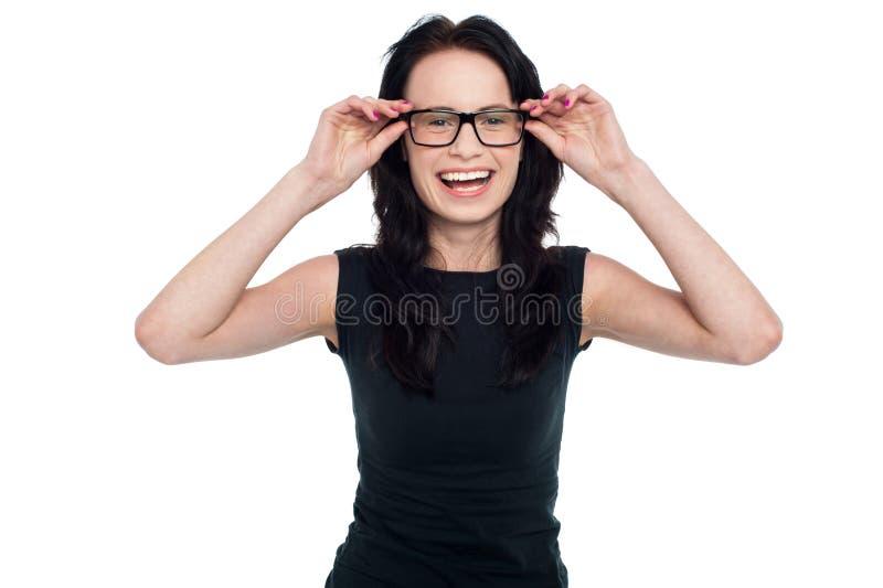 Reizend Dame, die ihre Brillen justiert lizenzfreie stockfotografie