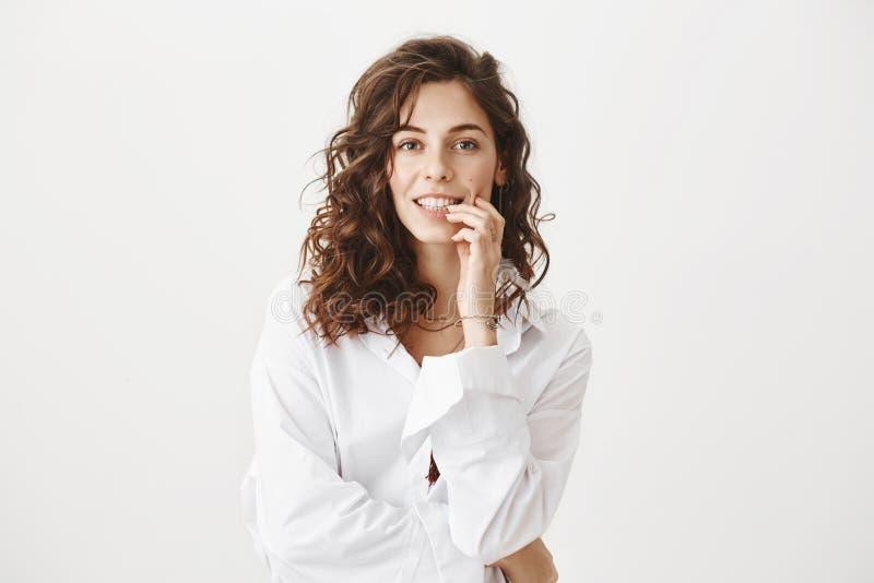 Reizend erwachsene kaukasische Frau, die Finger auf Lippe beim Kamera verlockend lächeln und betrachten, seiend in romantischem h lizenzfreie stockfotografie