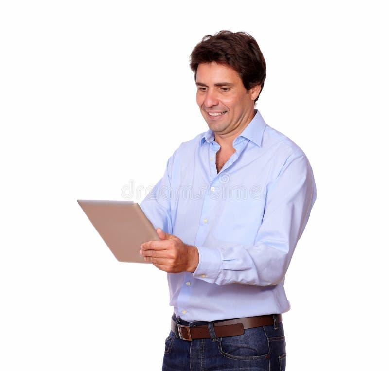 Reizend erwachsener Mann, der an Tabletten-PC arbeitet stockbild