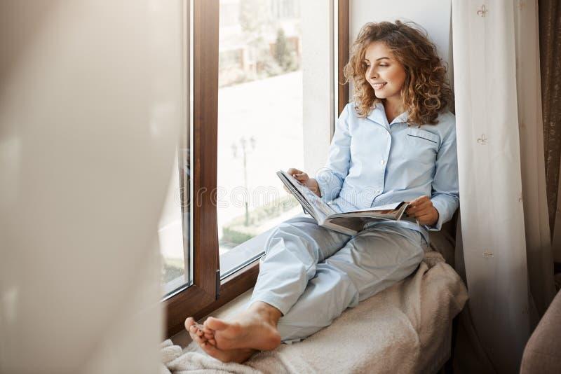 Reizend Geschäftsfrau, die entspannende Zeit zu Hause hat Erfreute schöne erwachsene Frau im Nachtzeug, das auf Fenster sitzt lizenzfreies stockbild