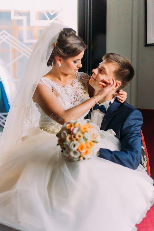 Reizend junge Braut, die auf Knien ihres liebevollen Bräutigams in einem luxuriösen Stuhl mit glänzenden Fenstern als Hintergrund lizenzfreies stockfoto